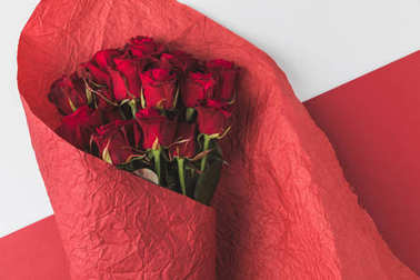 top view of bouquet of roses in red wrapping paper isolated on white