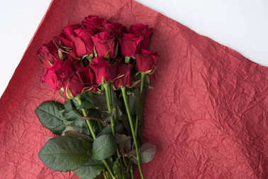 top view of bouquet of roses on red wrapping paper isolated on white