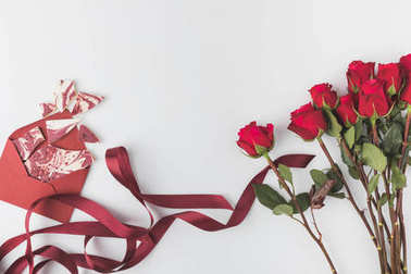 flat lay with arrangement of red roses with ribbon and envelope with sweet dessert isolated on white, st valentines day concept