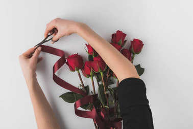 cropped shot of woman decorating bouquet of red roses with ribbon for st valentines day holiday isolated on white