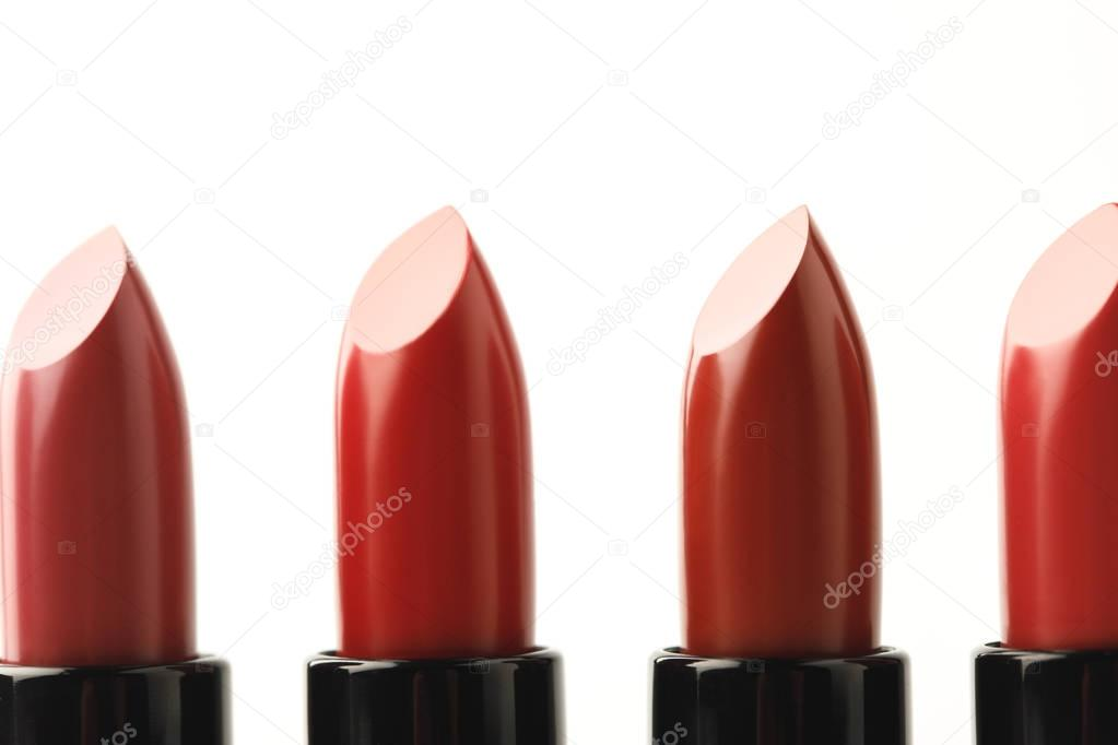 close-up shot of row of lipsticks of various shades isolated on white
