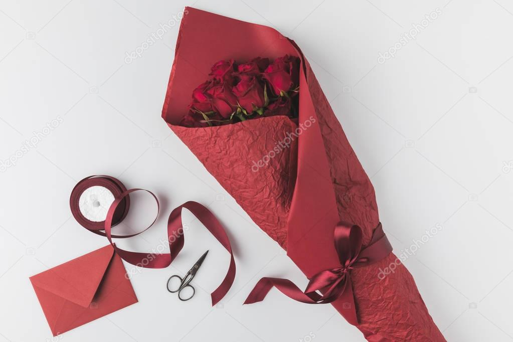 flat lay with bouquet of roses, ribbon and envelope isolated on white, st valentines day holiday concept