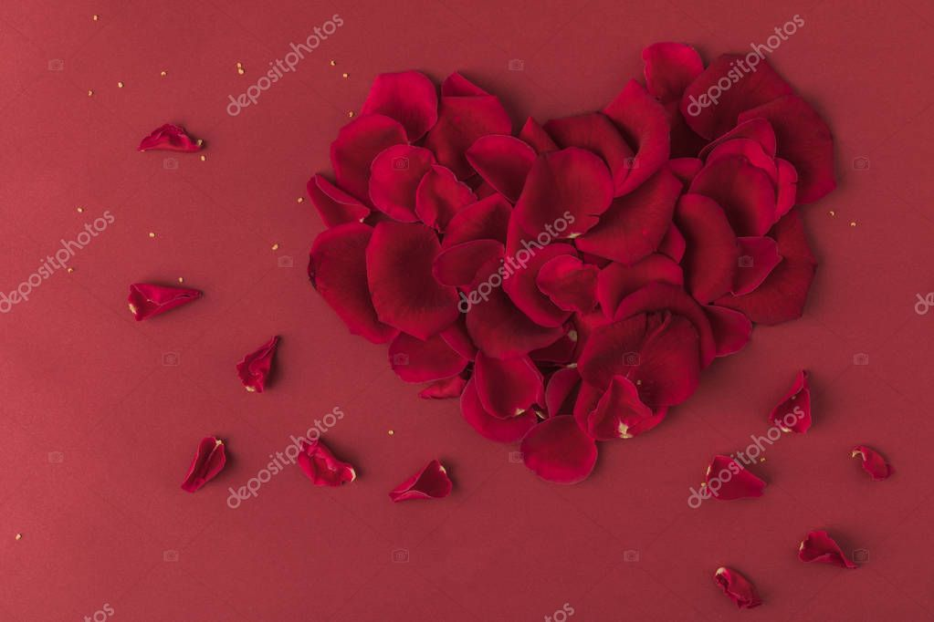 top view of heart made of roses petals isolated on red