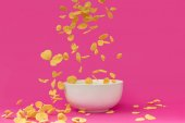 Photo close-up view of delicious crunchy corn flakes falling into white bowl isolated on pink