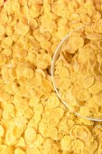 top view of tasty crispy corn flakes and white bowl