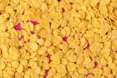 Photo top view of delicious tasty crispy corn flakes on pink