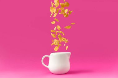 close-up view of organic corn flakes falling into milk jug isolated on pink