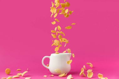 close-up view of crispy corn flakes falling into milk jug on pink