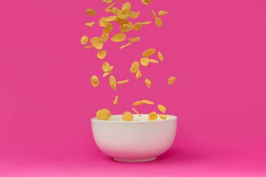 close-up view of delicious corn flakes falling into white bowl isolated on pink