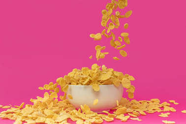 close-up view of sweet delicious corn flakes falling into white bowl on pink