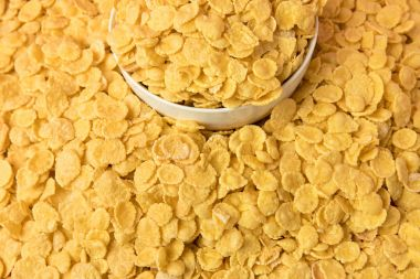 close-up view of tasty crispy corn flakes and white bowl