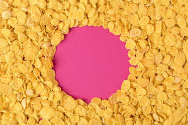 top view of circle made in healthy organic corn flakes on pink