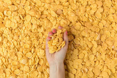 top view of female hand holding crunchy organic corn flakes