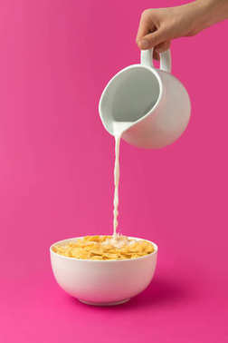 cropped shot of person pouring fresh healthy milk from jug into bowl with corn flakes isolated on pink