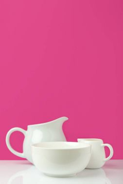 close-up view of empty white bowl, big jug and milk jug on pink