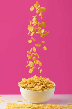 close-up view of tasty corn flakes falling into white bowl on pink