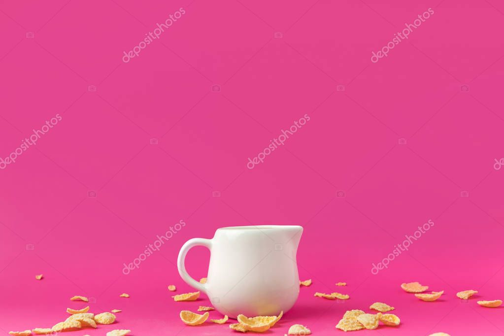 close-up view of jug with milk and crunchy corn flakes on pink