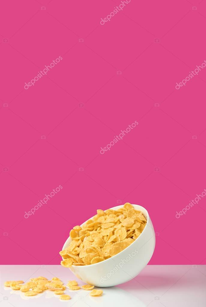 white bowl full of healthy tasty corn flakes on pink