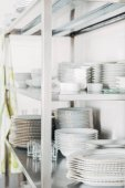 close-up shot of stacked clean tableware on shalves at restaurant