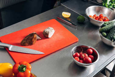 sliced meat on cutting board with vegetables at restaurant kitchen