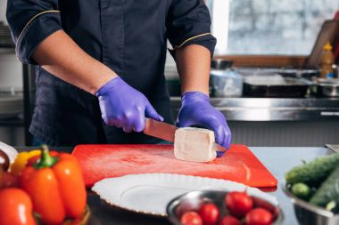 cropped shot of chef slicing cheese at kitchen