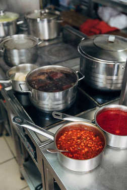 various food in sauce pans at restaurant kitchen