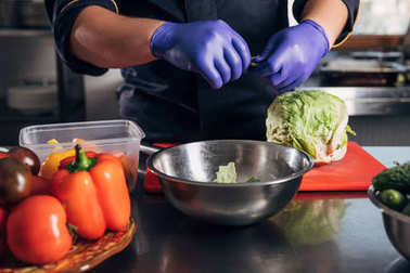 cropped shot of chef cooking vegetables at workplace in restaurant