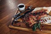 Fotografie Detailní záběr grilovaný steak podávaný s omáčkou a granátové jablko semena na dřevěné desce
