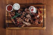 various grilled meat served on wooden board with sauces