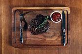pohled shora grilovaný steak s příbory a omáčkou na dřevěné desce
