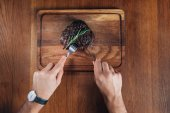 Photo cropped shot of man cutting grilled steak on wooden board