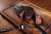 Fotografie zblízka střílel z lahodné středně krvavý steak grilovaný na dřevěné desce
