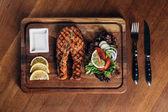 felülnézet grillezett lazac steak tálalva fából készült táblán szelet citrom és saláta