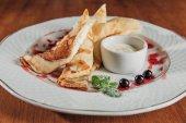 Fotografie köstliche gerollte Crepes mit Quark mit Marmelade auf weißen Teller serviert