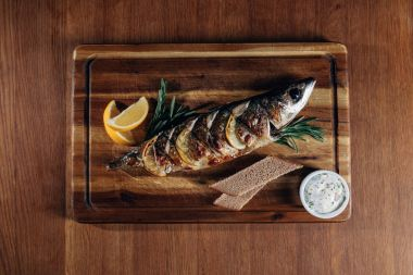 top view of grilled fish with lemon and rye bread on wooden board