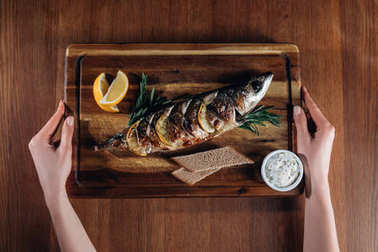 cropped shot of woman holding grilled fish with lemon on wooden board