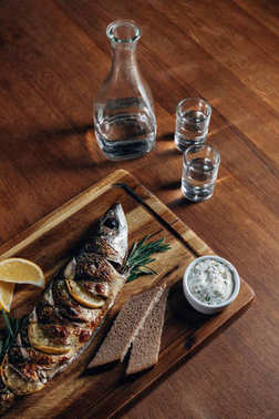 close-up shot of grilled fish with lemon on wooden board with vodka in decanter and shots