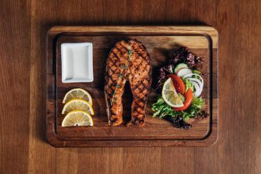 top view of grilled salmon steak served on wooden board with lemon and salad