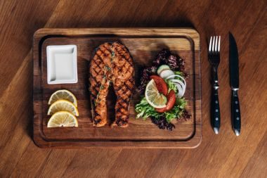 top view of grilled salmon steak served on wooden board with lemon slices and salad