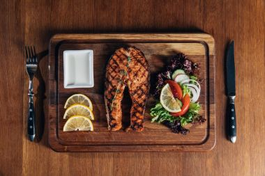 Top view of delicious grilled salmon steak served on wooden board with lemon and lettuce stock vector