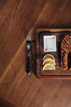 top view of grilled salmon steak served on wooden board with lemon slices