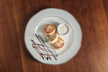 top view of delicious cottage cheese pancakes on white plate