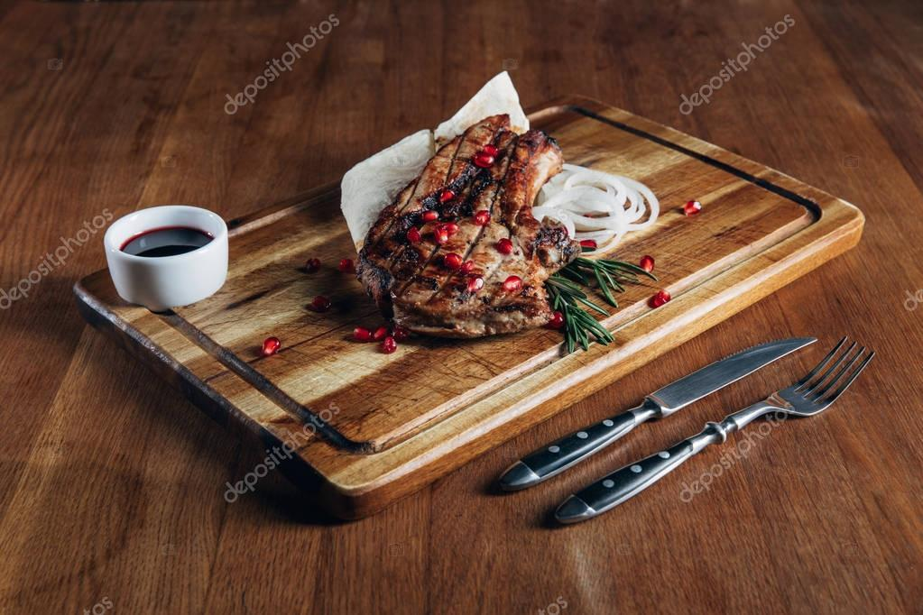 delicious grilled steak served with sauce and pomegranate seeds on wooden board