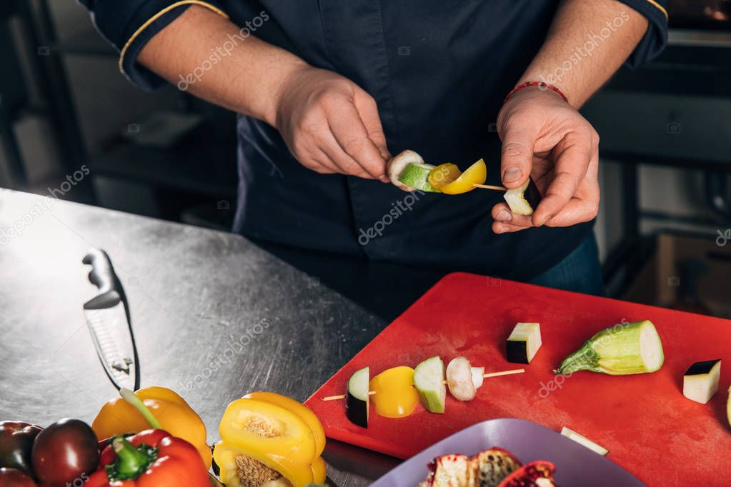 cropped shot of chef piercing vegetables on sticks for grill