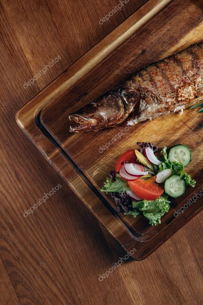 top view of grilled fish with salad on wooden board