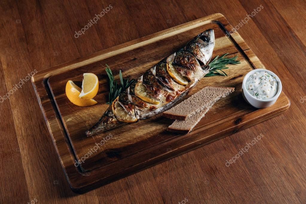 delicious grilled fish with lemon on wooden board
