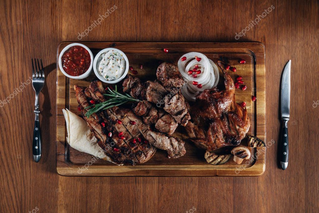 assorted grilled meat served on wooden board with sauces