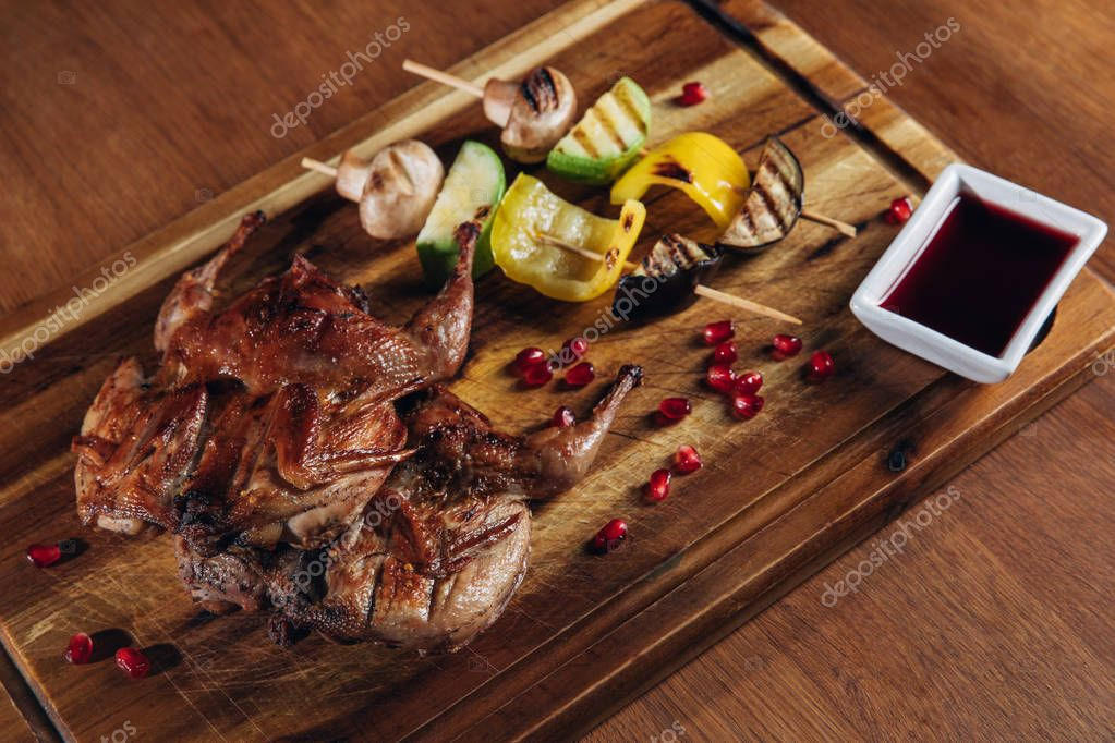 close-up shot of roasted quail with vegetables served on wooden board