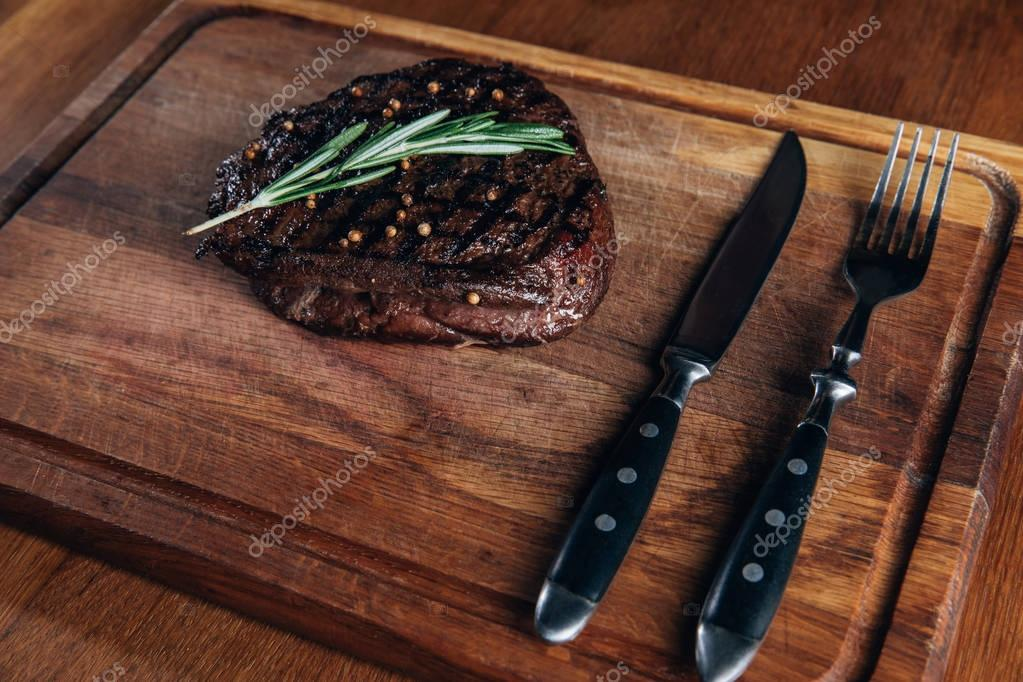 delicious grilled steak with cutlery on wooden board