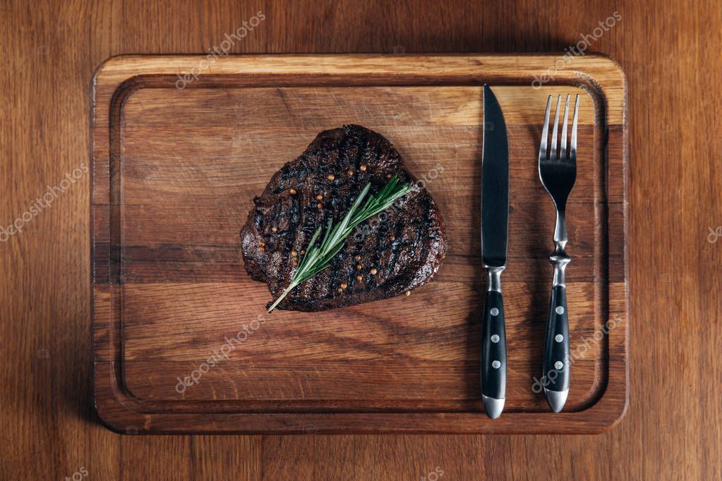 top view of grilled steak with cutlery on wooden board